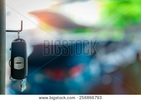 Black And Silver Car Key Hang On Metal Pole On Blurred Background Of Luxury Blue Suv Car. Car Rental
