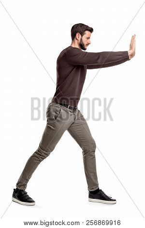 A Bearded Man In Casual Clothes Tries To Push A Heavy Object With Both Arms With One Leg Put In Fron