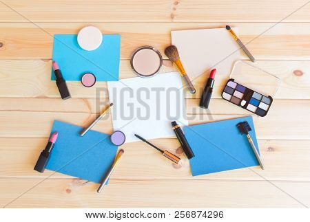 Paper Cards, Makeup Cosmetics And Brushes On Wooden Background