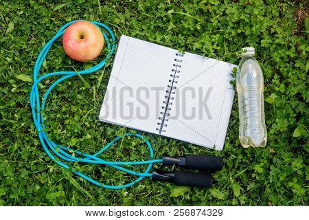 Bottle Of Water, Notebook, Apple And Skipping Rope On Fresh Green Grass. Top View, Copy Space.