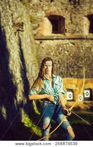 Archer, Woman Or Cute Girl With Long Hair And Blue Jean Clothes Holding Bow And Arrow On Sunny, Summ
