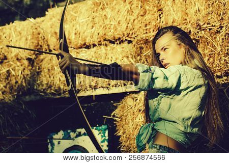 Girl Or Cute Woman, Archer Or Hunter, With Long Hair Shooting With Bow And Arrow On Sunny Day At Arc