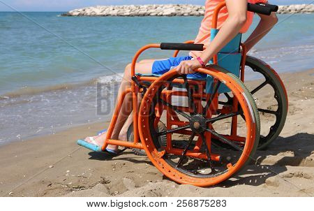 Young Boy On The Wheelchair In Summertime On The Beach