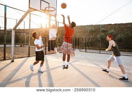 Group of young sporty multiethnic men basketball players playing basketball at the sport ground