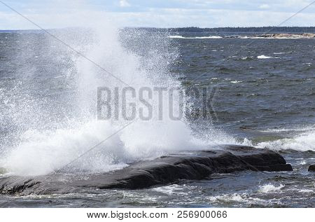 Powerful Gale Wind Along The Coastal Area. Waves, Breakers Hit The Coast, Shore And Rocks.