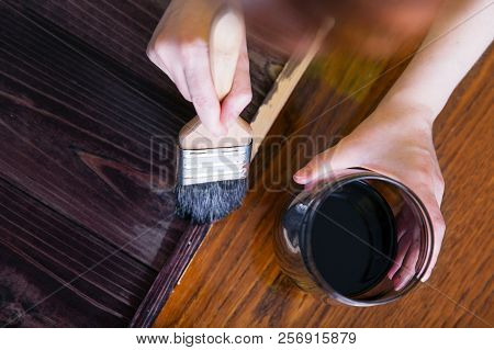 A Woman Paints By Hand The Planks Of Stained Ebony Wood. Top View
