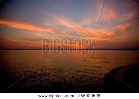 Beautiful Sunset. Blurred Shot Of The Dramatic Sunset On The Lake. Dramatic Clouds As A Defocused Na