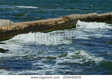 Long Gray Stone Concrete Pier In Sea Waves And Foam