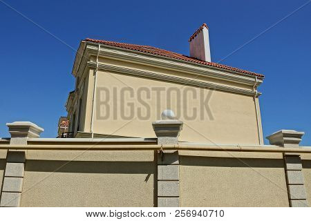 Wall Of A Brown House With A Red Roof Behind A Concrete Fence