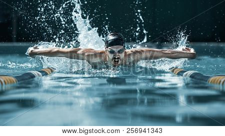 The Dynamic And Fit Swimmer In Cap Breathing Performing The Butterfly Stroke At Pool. The Young Man.