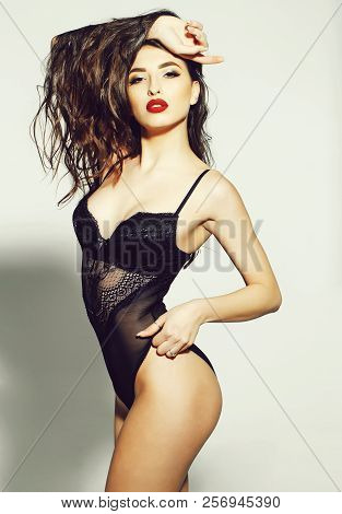 Pretty Woman Or Cute Sexy Girl In Erotic Black Bodysuit With Long Curly Brunette Hair, Has Red Lips