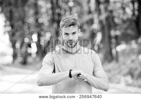 Man Athlete On Strict Face Setting Up Fitness Tracker, Nature Background. Athlete With Bristle With