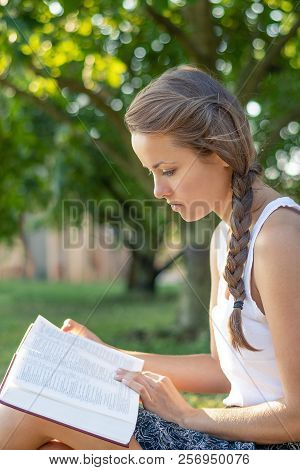 Christian Worship And Praise. A Young Woman Is Reading The Bible In The Early Morning With Sun In Th