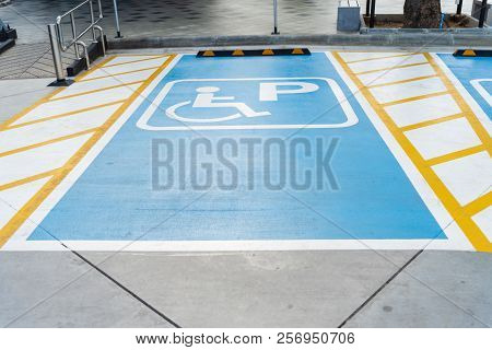 International Handicapped (wheelchair) Or Disabled Parking Symbol Painted In Bright Blue On Parking