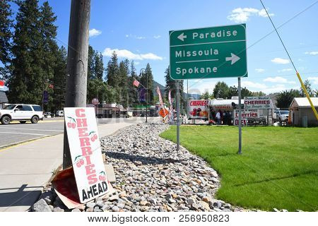 ST. REGIS, MONTANA, USA: September 1, 2018: Sign points to Paradise, Missoula and Spokane with a cherry stand in behind it