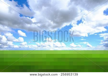 Blue Sky Over Green Meadow. On Blue Sky With Large Cumulus Clouds. Below Is A Green Meadow With Smal