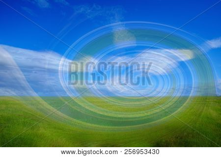 Blue Sky With Clouds Over Green Meadow Through A Translucent Helix. On Blue Sky With Large Cumulus C