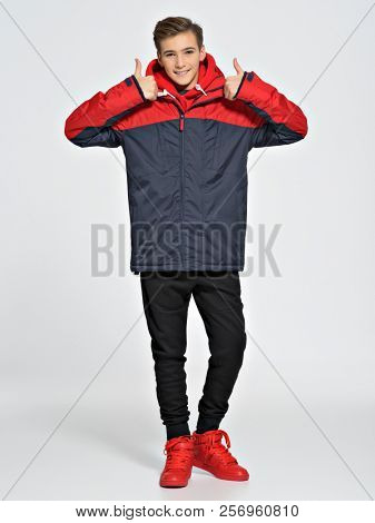 Teenage boy dressed in a sport wear. Teenager wears fashionable fall clothes and shows thumbs up - posing over white background. Full portrait.