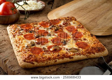 A Delicious Square Crust Flatbread Pizza With Pepperoni, Bacon And Mushrooms On A Rustic Wood Table