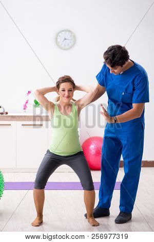Pregnant woman doing physical exercies with instructor
