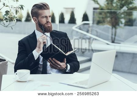 Handsome Businessman Working Laptop Cafe Outdoors. Writing Note. Bearded Serious Man Wearing Suit An