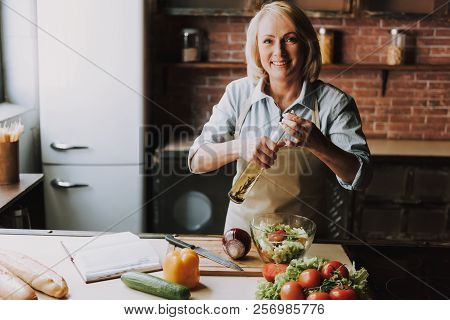 Senior Woman Cooking Salad In Kitchen At Home. Grandma Cooking Food. Healthy Food Concept. Vegetable
