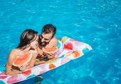 Cute picutre of young man and woman leaning to air mattress and hold pieces of watermelon. They look at eac other and smile. Couple is in swimming pool. poster