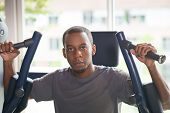 Black man training on pec deck fly machine and looking at camera. Young guy wearing t-shirt with window in background. Bodybuilding and wellness concept. Front view. poster