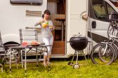 Family vacation travel RV, holiday trip in motorhome, Caravan car Vacation. Picnic with outdoor barbecue. Woman pours a glass of orange juice poster