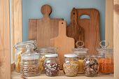 Glass jars with different foodstuff and cutting boards on shelf indoors poster
