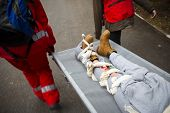 Paramedics from mountain rescue service provide first aid during a training for saving a person in accident with broken leg. Blurred motion. poster
