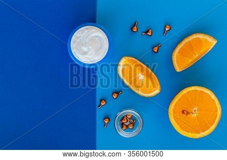 Vitamin C, Natural Anti Aging Cosmetics Serum And Syringe With Ornge Fruit Slices.cream With Oranges