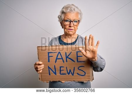 Senior grey-haired woman holding banner with fake news message over white background with open hand doing stop sign with serious and confident expression, defense gesture
