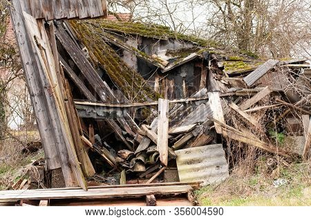 Ruin Of An Old Damaged Wooden Hut, Collapsed On A Farmyard