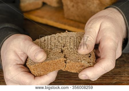 A Single Piece Of Bread In The Hands Of A Man. Mens Hands Break A Loaf Of Bread. An Adult Man Breaks