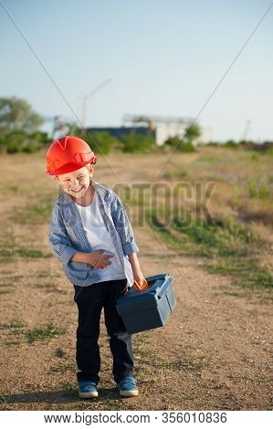 Payday Concept Of Happy Laughing Small Kid In Orange Helmet With Tool Box Walking From Work Place At