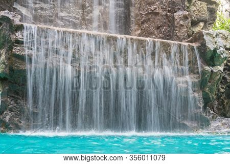 Landscape Of Beautiful Artificial Waterfall In Garden At The Public Park