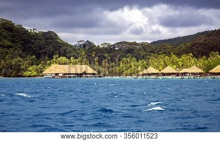 Luxury Overwater Thatched Roof Bungalow Resort On A Wooden Pontoon In The Rays Of Sunrise On Bora Bo
