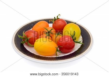 Macro Photo Of A Plate With Bright Colored Tomatoes On A White Background