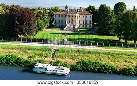Aerial Top View Of Ancient Villa Giovanelli, Garden And Houseboat Barge On Canal Brenta From Above,