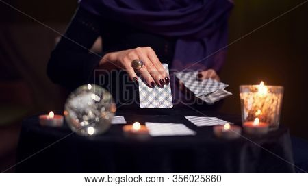 Close-up of woman fortuneteller hand with cards while sitting at table with candles in dark room
