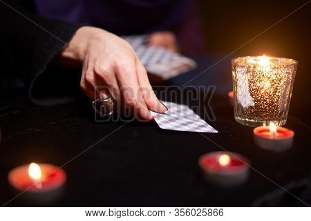 Fortuneteller divines on cards sitting at table with burning candles