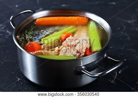 Slow-cooked Fish Broth Or Soup Of Salmon, Onion, Carrot, Celery, Herbs And Spices In A Stockpot On A
