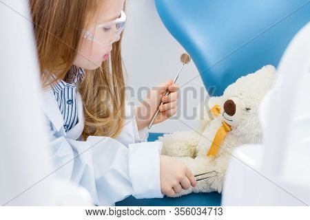 Little Cute Girl In White Doctor Robe Uniform And Protective Glasses Is Treating With Instruments, T