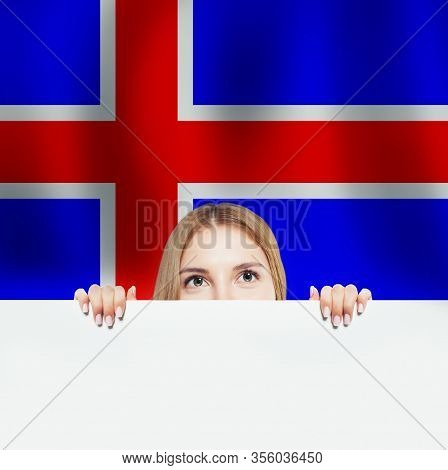 Iceland Concept. Happy Woman With White Banner And The Icelandic Flag Background. Travel And Learn I