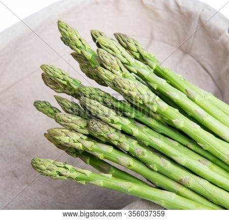 Bunches of asparagus tied on a burlap background.