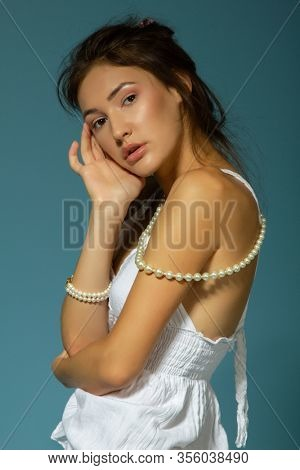 Beautiful girl in white dress and pearl beads posing over blue background. Portrait of charming young woman