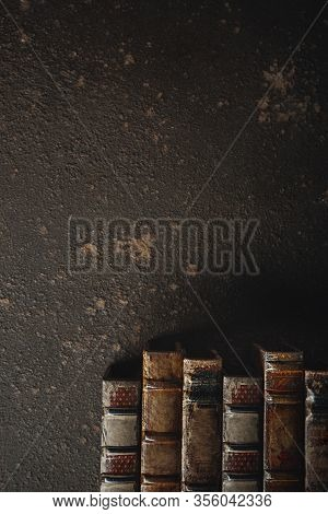 Old Fashioned Flat Lay With Stack Of Antique Leather Bound Books Against A Dark Background. Literatu