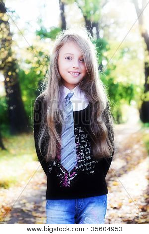 Little charming blonde girl during her walk in a park