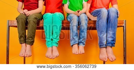 Children Are Sitting On The Table, Legs Hanging Down. Four Teenage Children Show Their Knees And Leg